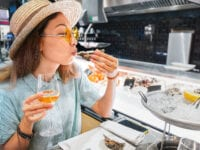 Asian woman tasting fresh raw oyster shellfish and drinking wine in seafood restaurant
